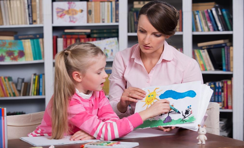 Woman with young girl painting