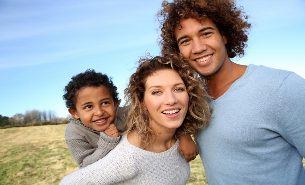 Family of three smiling outside